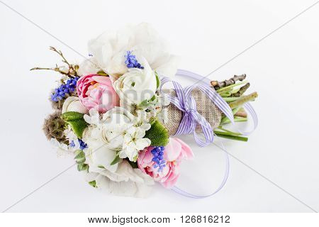 Bouquet from pink tulips violet grape hyacinths white anemones violet veronica and white buttercup with violet ribbon lying on white background