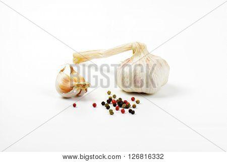 fresh garlic and peppercorns on white background