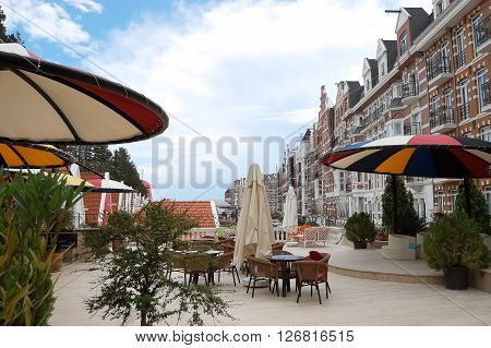 Kemer, ANTALYA, TURKEY - MAY 30, 2015: Street with original buildings and colored umbrellas in hotel Orange County Resort, Turkey.