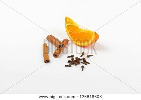 slice of orange, cinnamon sticks and cloves on white background