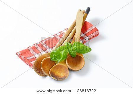 old wooden spoons and fresh basil on checkered dish towel