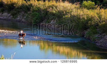 BIG BEND NATIONAL PARK, TEXAS - APRIL 3: Mexican national on horseback rides through the Rio Grande River at Big Bend National Park on April 4th, 2016.