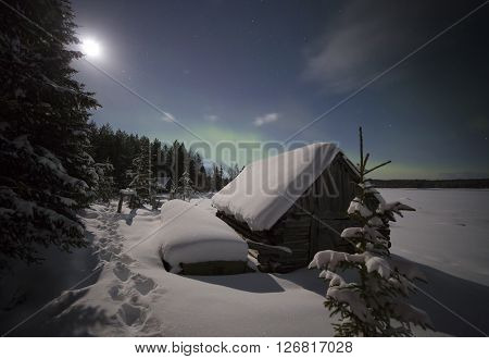 Village house in the lights of moon and Aurora borealis. Northern Karelia. Russia.