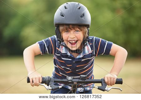 Kid with bike and helmet smiles while having fun