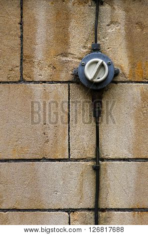 Old retro style vintage electrical light switch ON OFF with black wires on a old stone wall background