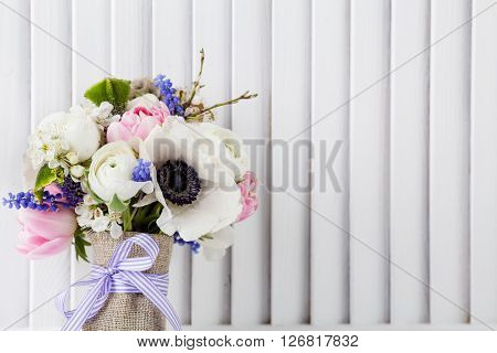 Pastel bouquet from pink tulips violet grape hyacinths white anemones violet veronica and white buttercup with violet ribbon with white wooden shutter background