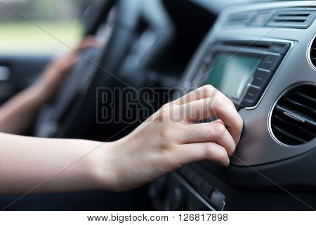 woman turning button of radio in car