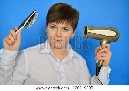Boy teenager with a comb and a hair dryer