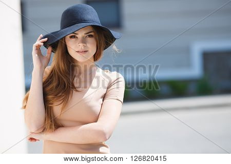 Young beautiful woman brunette with long straight hair and brown eyes,dressed in a beige blouse with short sleeves, wears a dark blue hat with large brim, poses for photographer in the summer outdoors