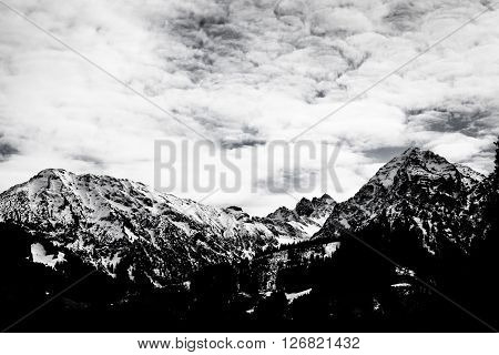 Snowcapped mountain range with clouds in black and white