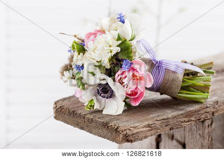 Bouquet from pink tulips violet grape hyacinths white anemones violet veronica and white buttercup with violet ribbon lying on the old wooden bench with white background