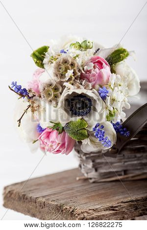Bouquet from pink tulips violet grape hyacinths white anemones violet veronica and white buttercup with violet ribbon lying in the basket on the old wooden bench with white background