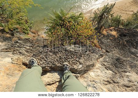 close up of hiking legs on seaside cliff