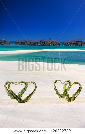 Heart Made Of Palm Tree Leaves On Tropical Island With Overwater Bungalows In The Background.