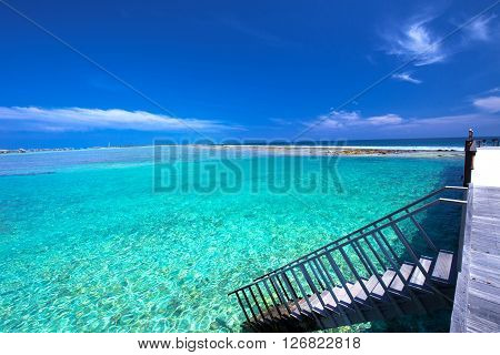 Tropical island with sandy beach with palm trees and tourquise clear water