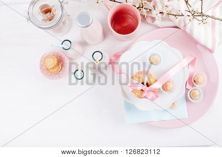 Four bottles of milkshakes three with straws jar full of candies pink cup and glass of milk and plates with cookies and biscuits tied with pink ribbon and cloth with spring blossom plum tree and little flowers on white wood from the top