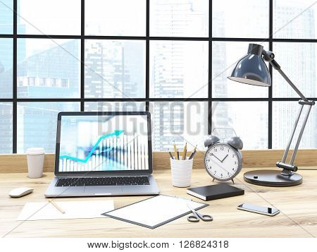 Frontview of office desk with business chart on laptop screen alarm clock lamp and other items with buildings in the background. 3D Rendering