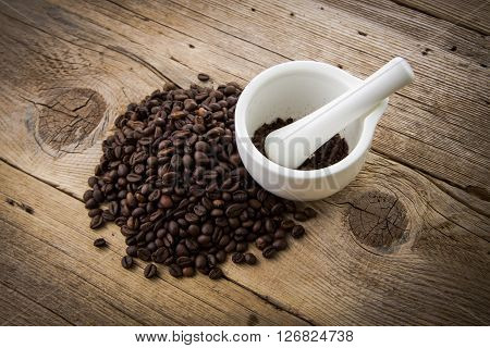 Coffee Beans On Wooden Background And White Mortar