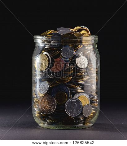 Jar of Money Isolated on a black Background.