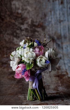 Bouquet from pink tulips violet grape hyacinths white anemones violet veronica and white buttercup with violet ribbon standing on rought rusty metal background