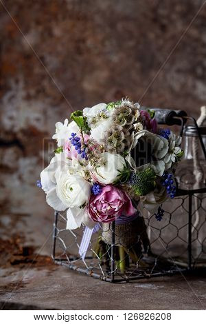 Bouquet from pink tulips violet grape hyacinths white anemones violet veronica and white buttercup with violet ribbon lying in the metal basket with glass bottle in rought rusty metal environment