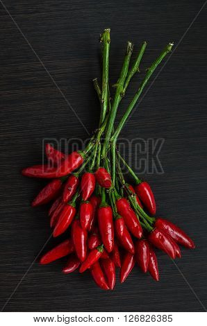 Red hot mini chili peppers over dark wooden background. Overhead view of chili pepper on wood background. Dark food photography with bunch of red chili. Top view.