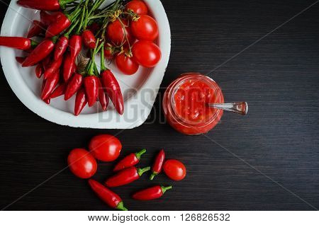 Tomato ketchup sauce with cherry tomatoes and mini red hot chili peppers in a small glass jar with a spoon on dark wooden background. Homemade tomato sauce and fresh tomatoes. Top view. Copy space.