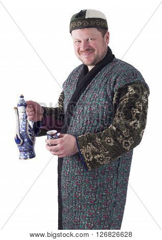 Man in traditional oriental robe with ornamental bowl on white background