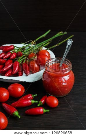 Glass jar of homemade tomato sauce with fresh ingredients on dark wooden background. Natural homemade sauce of tomatoes, peppers and vegetables. Chilli jam. Selective focus.