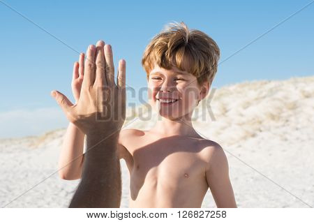 Young boy giving high five to father. Close up of son enjoying holidays at beach with father. Happy smiling child giving a high five his dad at beach.