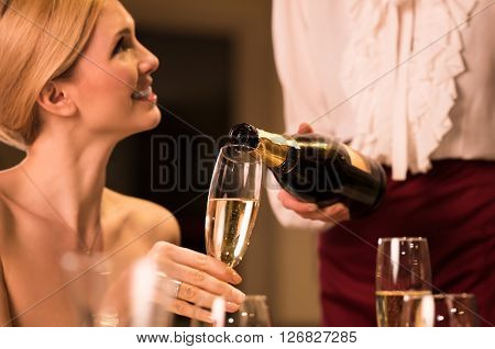 Young waitress pouring champagne in glass. Happy young woman holding champagne glass while waitress filling the glass. Young woman enjoying at restaurant.