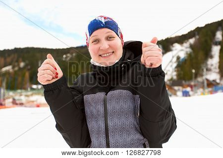 Ski holidays. Sport woman. Thumb up. Female wearing sports jacket. Young cheerful woman outdoors in winter. Young woman on ski vacation. Thumbs up. Winter sport woman.