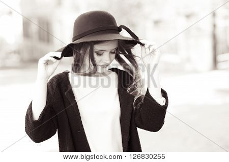 Smiling teen girl wearing stylish coat and hat outdoors. Black and white photo.