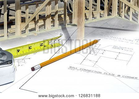 Blueprints With Hardhat, Workgloves And Reading Glasses With Wood Framed Structure
