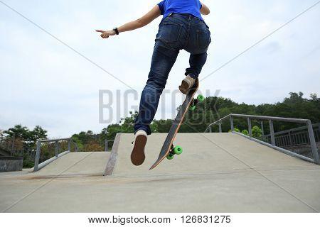 young woman skateboarder skateboarding at skate park