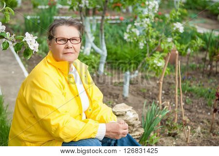 Woman in her spring garden resting sitting