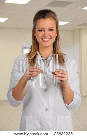Portrait of medical lab worker holding glassware inside building