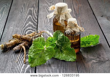 Medicinal plant - a burdock. The roots and leaves of burdock burdock oil in bottles on a wooden background. It is used for the treatment and care of hair