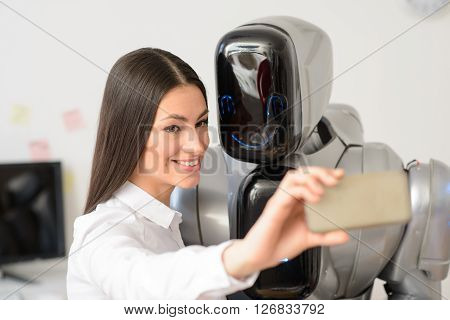 Have some fun.  Cheerful beautiful  nice girl holding cellphone and making selfies  with the robot