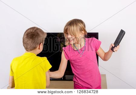 Siblings arguing over the remote control in front of the television.