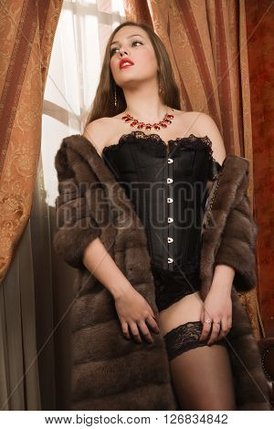 Beautiful And Sexy Brunette Young Woman Wearing Black Lingerie, Fur Cape And Stockings