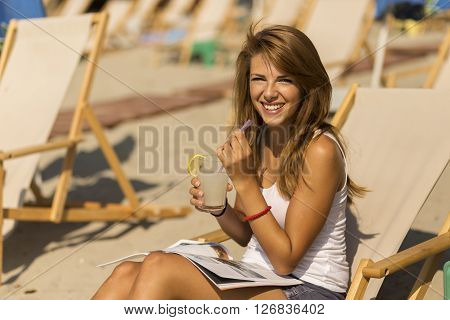 Attractive brunette lying on a sunbed on a beach drinking lemonade reading a magazine and enjoying the sun