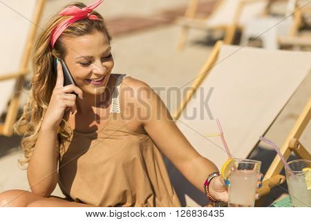 Pretty blond girl sitting on a sunbed on a beach having a conversation on mobile phone and smiling