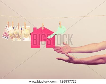 Concept of real estate and deal. Hands of seller man with house model and money banknotes. Selling and buying proposition.