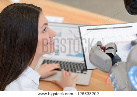 Curious glance. Cheerful delighted positive beautiful girl  sitting at the table and using laptop while looking at the robot who is holding calendar