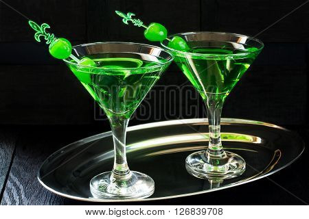Green cocktail with maraschino cherry in a martini glasses on a metal tray and dark background