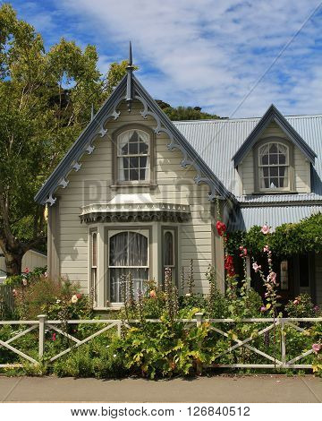 Old house in Akaroa. Beautiful small house with flowers in the front. Scene in Akaroa, New Zealand.