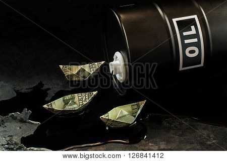 Oil business concept. The ships of the dollars floating on oil flowing out of the barrel