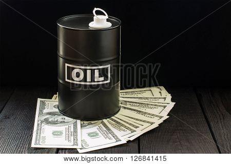 Oil business concept. Barrel of oil on dollar bills on a dark wooden background