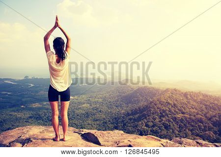 young woman practice yoga at mountain peak cliff ** Note: Visible grain at 100%, best at smaller sizes